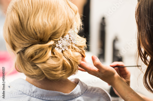 Obraz na plátně  Hair stylist makes the bride before a wedding