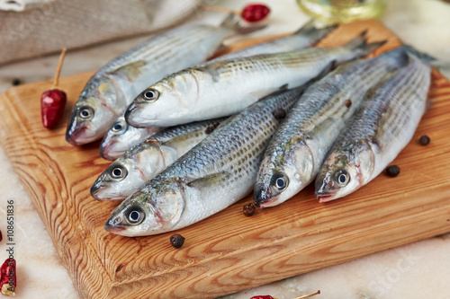 Seafood - fresh  fish  mullet with spices  on the catching board. Canvas Print