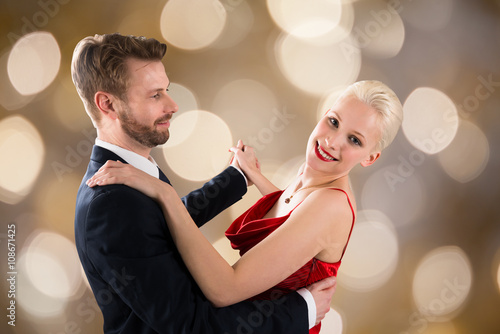 Foto op Canvas Dance School Young Couple Dancing On Bokeh Background