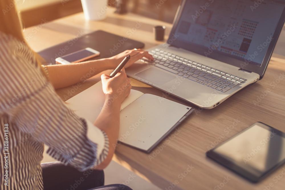 Fototapeta Female designer using laptop, sketching at blank notepad. Woman hand writing in notebook on wooden desk.