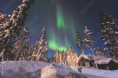 Poster Scandinavië Beautiful picture of massive multicoloured green vibrant Aurora Borealis, Aurora Polaris, also know as Northern Lights in the night sky over winter Lapland landscape, Norway, Scandinavia