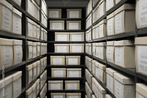 Photo Indoor storage details in a manufacturing enterprise, black shelves with white office boxes