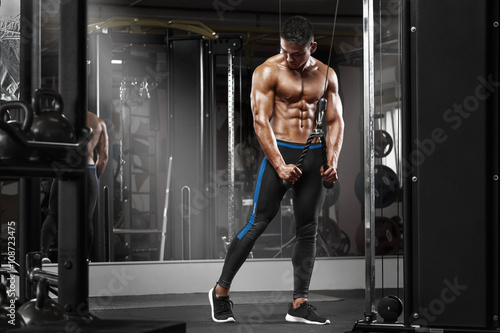 Muscular man working out in gym doing exercises at triceps, strong male naked torso abs