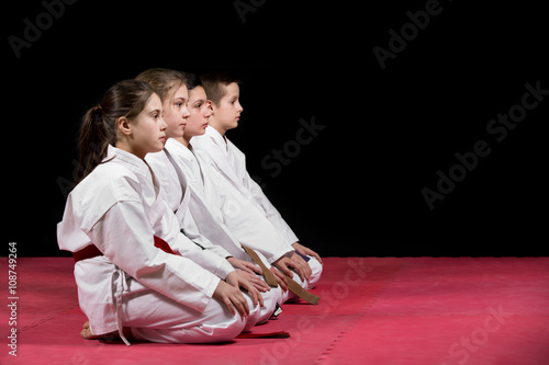Children in kimono sitting on tatami on martial arts seminar. Selective focus