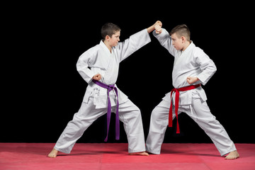 Fototapeta Two boys in white kimono fighting isolated on black background