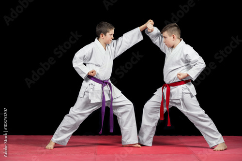 Two boys in white kimono fighting isolated on black background - 108751207