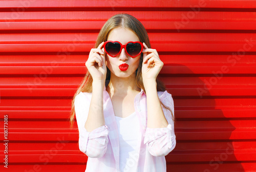 Fotografie, Obraz  Pretty woman in red sunglasses blowing lips kiss over colorful b