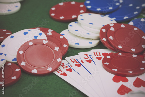 Poker chips and cards on a green table плакат