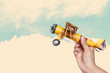 woman's hand holding toy airplane against blue sky, image is ret