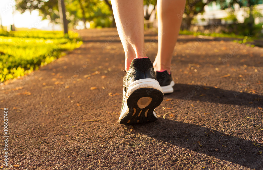 Fototapety, obrazy: Closeup of woman's feet walking in the park.