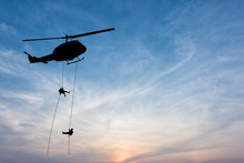 Silhouette Of Helicopter, Soldiers Rescue Helicopter Operations On Sunset Sky Background.