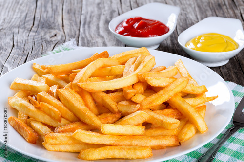 Photo  Tasty french fries on plate, on wooden table background