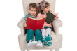 Children sit in a chair with books