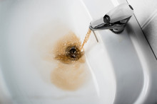 Dirty Brown Water Running Into A Sink