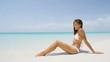 Beach body woman sun bathing on travel vacation. Sexy bikini body woman relaxing sun tanning lying down sunbathing on perfect paradise beach at tropical luxury destination in the Caribbean.