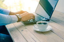 Coffee Cup With Closeup Man Typing A Laptop On Wooden Table.