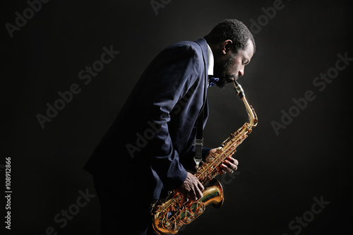 Photo  African American jazz musician playing the saxophone on grey background