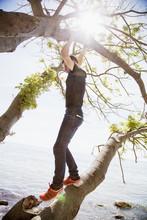 Teenage Boy Standing On Branch
