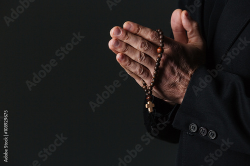 Fotografia, Obraz Hands of priest holding rosary and praying