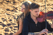 Beautiful Couple Violinist And Young Woman Together Over Sand Background