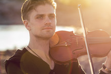 Handsome Young Man Violinist Over Picturesque Background