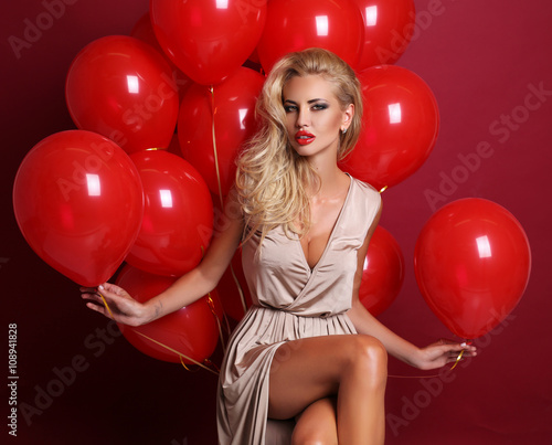 Photo  sexy woman with blond curly hair wears elegant dress, holding a lot of red air b