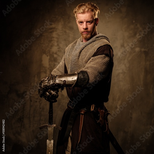 Photo  Young medieval knight posing on dark background.