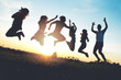 canvas print picture - Group of people jumping outdoors; sunset