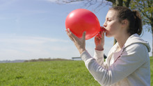 Female Blowing Up A Red Balloon