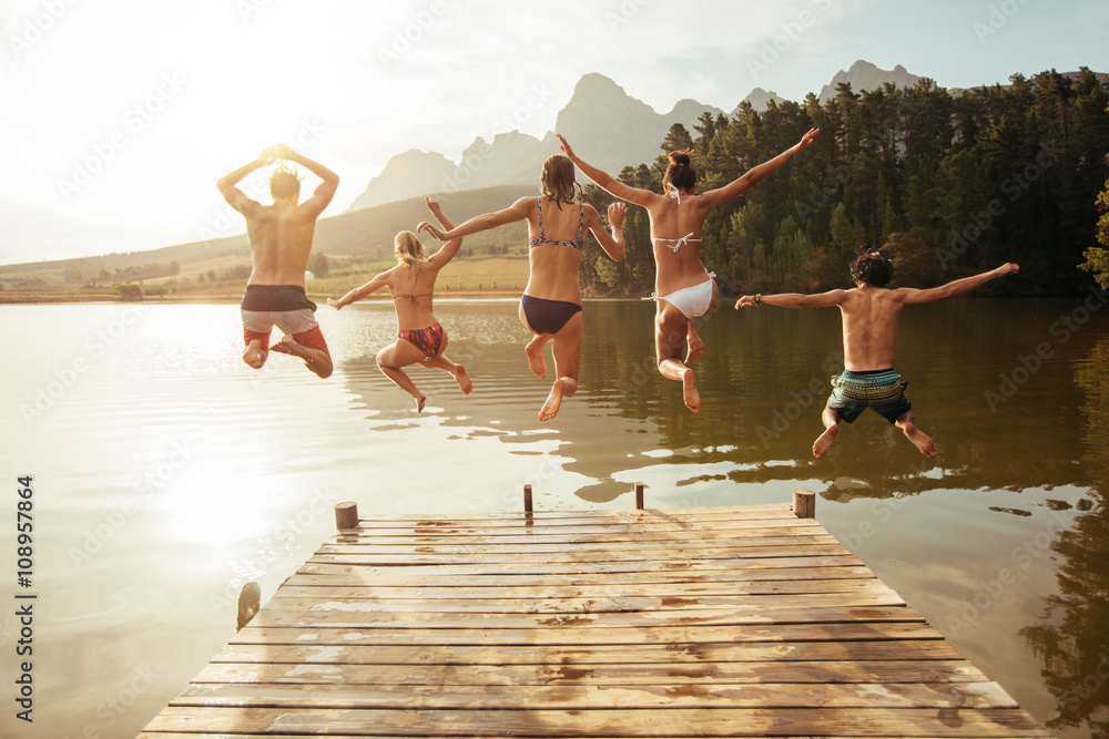 Fototapety, obrazy: Young friends jumping into lake from a jetty