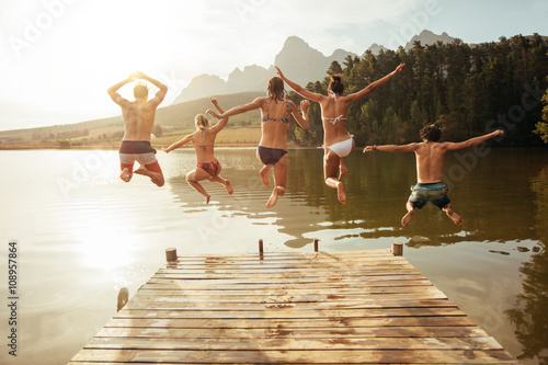 Vászonkép Young friends jumping into lake from a jetty