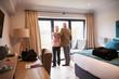 Senior Couple Arriving In Hotel Room On Vacation