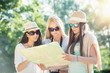 Three attractive girls looking for directions on a map at summer holidays, vacaton concept