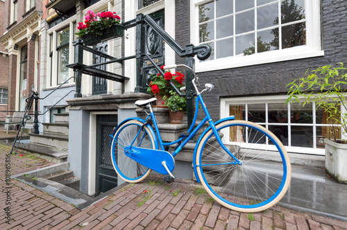 Photo  Blue classic dutch bicycle parked close a traditional house in Amsterdam, The Ne