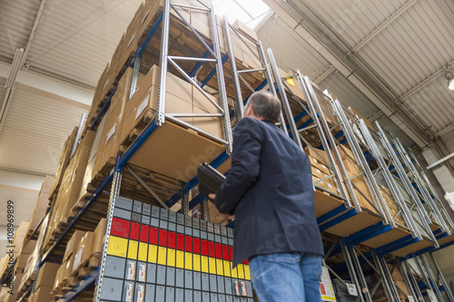 Manager checking goods in storage hall of factory Poster