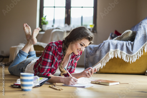 Young woman at home working with smartphone