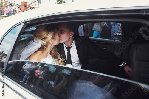 Photographie Happy romantic newlyweds kissing in wedding limo
