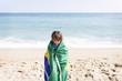 Little boy wrapped in Brazilian flag on a beach