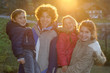 Group picture of four happy children and teenagers at backlight
