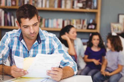 Foto  Close-up of man reading documents while family sitting in background at home