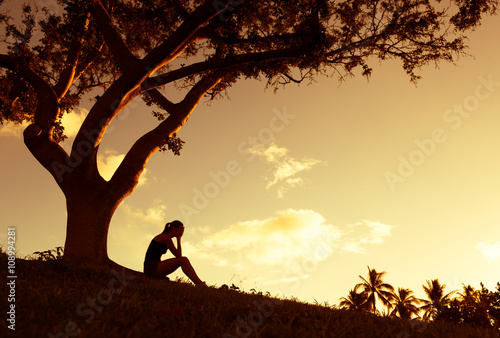 Photo Sad young woman sitting outdoors under a tree.