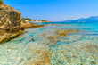 Crystal clear sea water of Lotu beach with tourist boat in distance, Corsica island, France