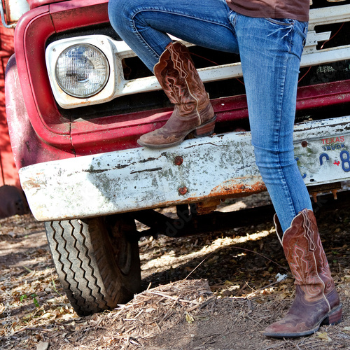 Valokuva  Western style image of cowgirl's legs in jeans and boots and old Texas truck on
