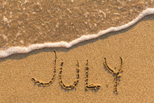 July - Word Drawn On The Sand Beach With The Soft Wave. Months Series Of 12 Pictures.