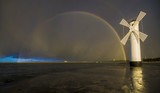 Fototapeta Tęcza - Tęcza nad wiatrakiem po przejściu wieczornej burzy nad morzem