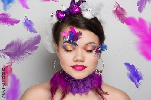 Circus Girl feathers, Close-up portrait of perfect woman faceart. Bright make up purple lips, pink shadows. Brown hair, birds violet feather & diamonds. New crazy art creative idea. Horizontal banner