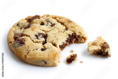 Photo  Single light chocolate chip cookie, bite missing with crumbs, is