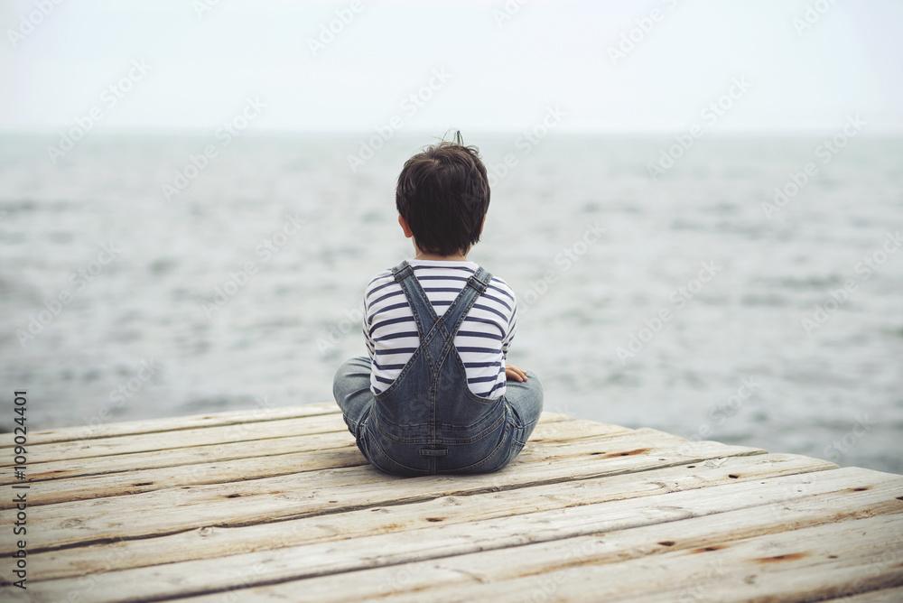 Obraz niño pensativo mirando el mar fototapeta, plakat