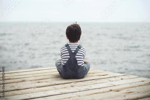 Fotografia  Rozważny chłopiec patrząc na morze