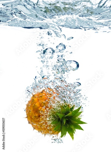 Spoed Foto op Canvas Opspattend water Bubbles forming in blue water after pineapple is dropped into it.